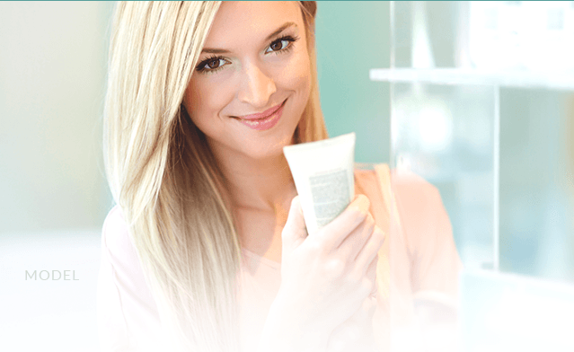 smiling blonde holding medical spa product
