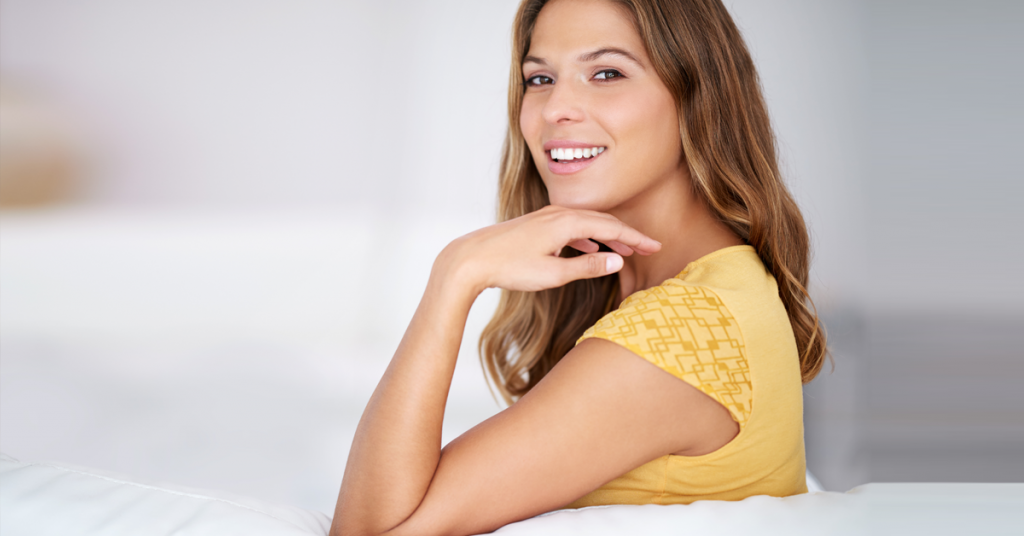Brunette women sitting on a couch and smiling.