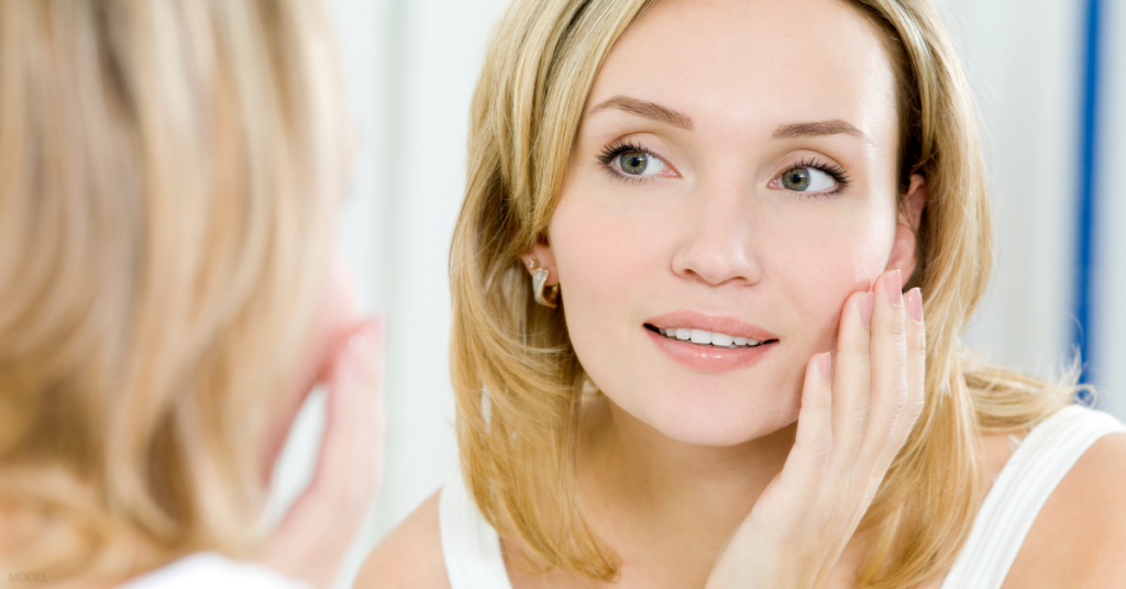 A woman looks in the mirror and ponders facial rejuvenation options.