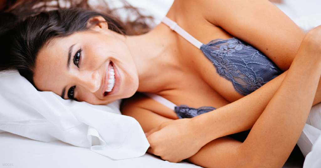 A woman rests in bed after a full recovery from a subtle breast augmentation procedure.