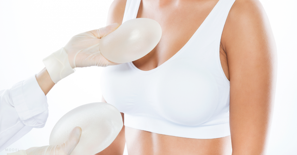 A woman evaluates implant options for her breast augmentation surgery.